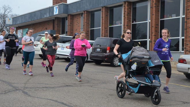 A group from Battle Creek's chapter of Moms Run This Town embarks on a run from the Battle Creek Y-Center.