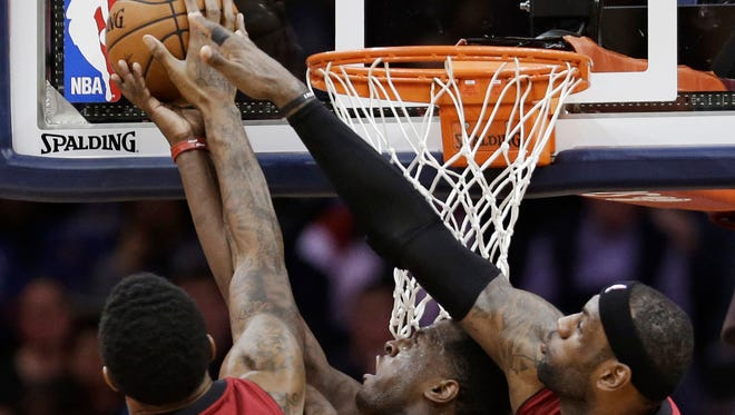 Miami's Udonis Haslem, left, and LeBron James, right, block a shot by Cleveland's Dion Waiters during the fourth quarter on Tuesday.
