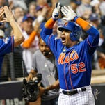 New York Mets' Travis d'Arnaud (7) greets Yoenis Cespedes (52) after Cespedes hit a fourth-inning, three-run home run during baseball's Game 3 of the National League Division Series, Monday, Oct. 12, 2015, in New York.