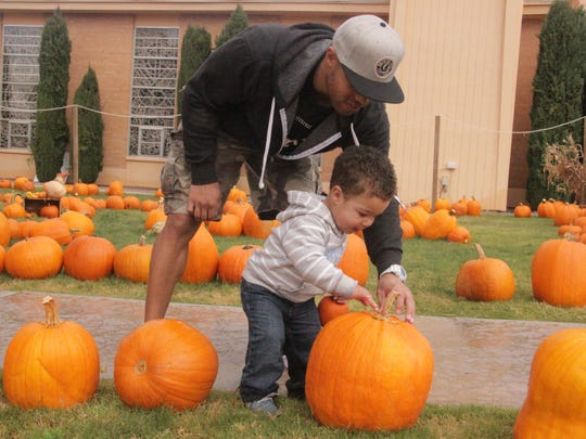 Theron McClinton shows his son, Blake McClinton, 1, pumpkins at the Grace United Methodist Church Pumpkin Patch Thursday morning.