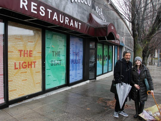From left, Warren Lehrer, design professor at SUNY and Brittany Brandwein, White Plains Business Improvement District, stand in front of the vacant stores on East Post Road in White Plains where SUNY design students have placed art work.