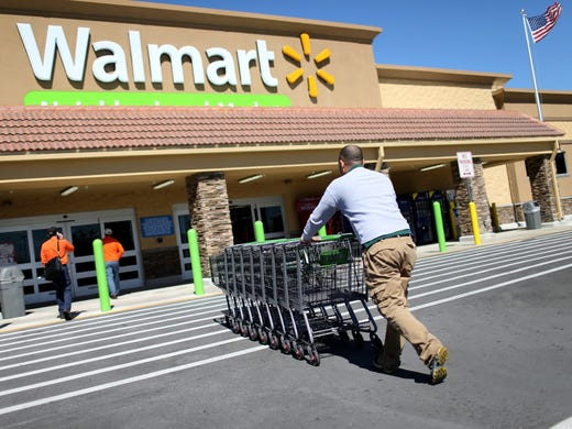 Walmart employee Yurdin Velazquez pushes grocery carts