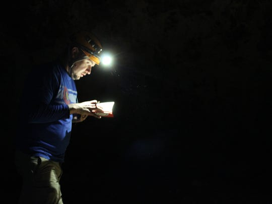 Zach Angstead records the dimensions of the Raynesford cave in a notebook. He will later transcribe his notes for the landowner.