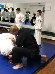 Jason Wesley helps one of his students work on their