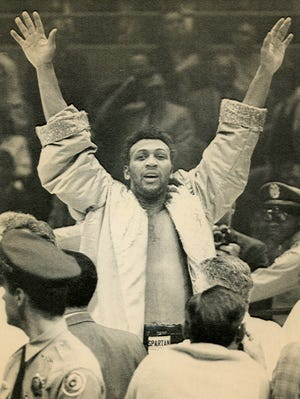 Jimmy Ellis jumps up and down with arms raised after gaining victory and the heavyweight title in 1968.