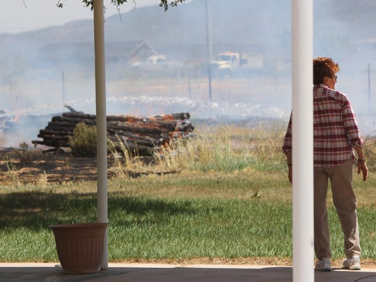 Carolyn Lincoln observes the damage from her back porch during a fire that occurred on her property on Friday, June 10, 2016.