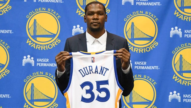 Kevin Durant poses for a photo with his jersey during a press conference after signing with the Golden State Warriors.
