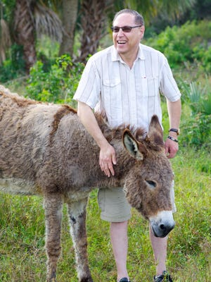Dave Pflaum pets Jesse, a donkey at the Friends for Animals Sanctuary in development in Cocoa. Pflaum, of Cocoa Beach, made a significant donation to the shelter.