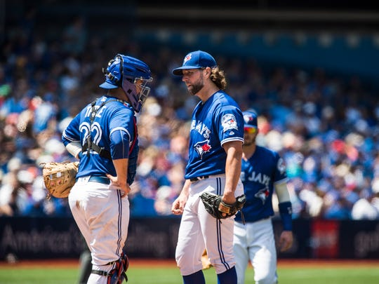 Toronto Blue Jays pitcher R.A. Dickey, right, talks to catcher Josh Thole before being pulled in the sixth inning of a baseball game against the San Diego Padres in Toronto, Wednesday, July 27, 2016. (Aaron Vincent Elkaim/The Canadian Press via AP)