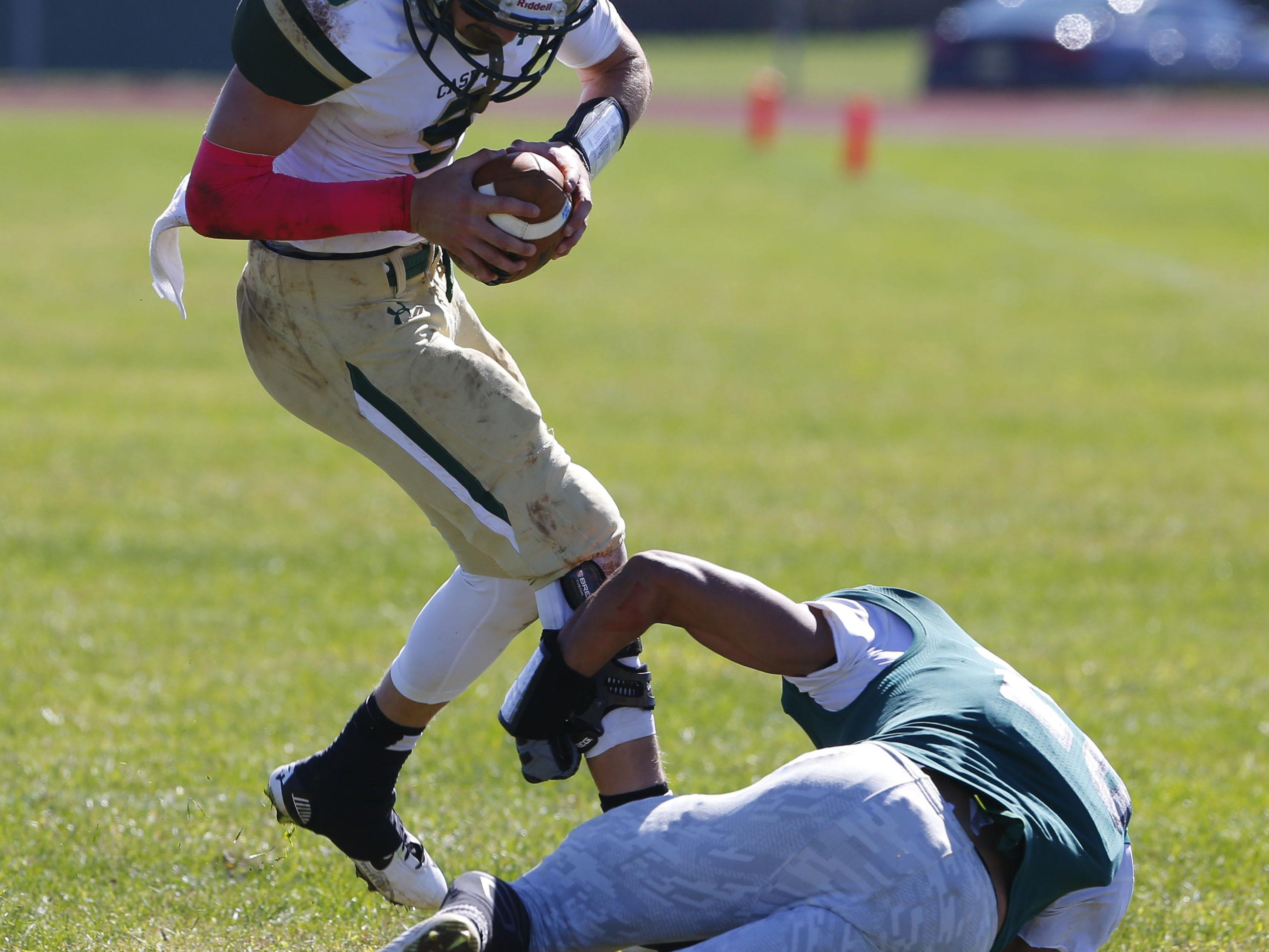 Red Bank Catholic quarter back Eddie Hahn (9) is tackle by Khaled Mostafa (28) of Colts Neck during game at Colts Neck High School, Colts Neck,NJ. Saturday, October 10, 2015.