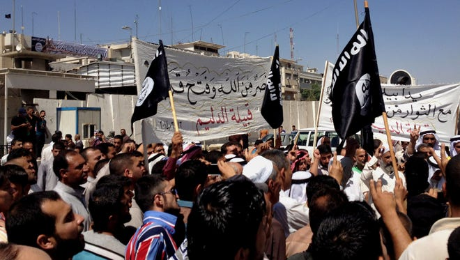 Demonstrators al-Qaeda flags in front of the government headquarters in Mosul.