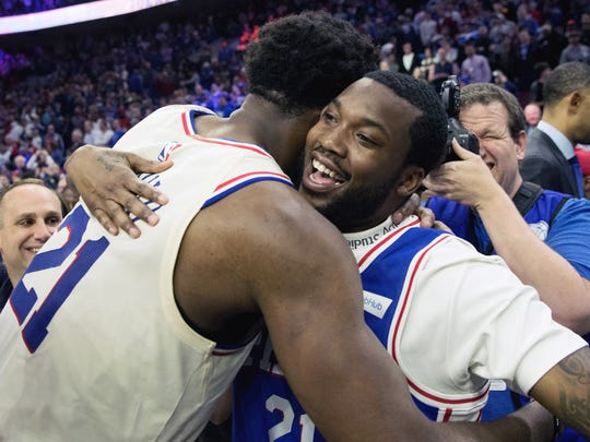 Philadelphia 76ers center Joel Embiid (21) hugs Meek Mill after a victory against the Miami Heat.