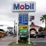 FILE - In this Feb. 27, 2015, file photo, a cyclist rides by a Mobil gas station in Los Angeles. Exxon Mobil Corp. reports quarterly financial results on Friday, July 31, 2015. (AP Photo/Nick Ut, File) ORG XMIT: NYBZ181