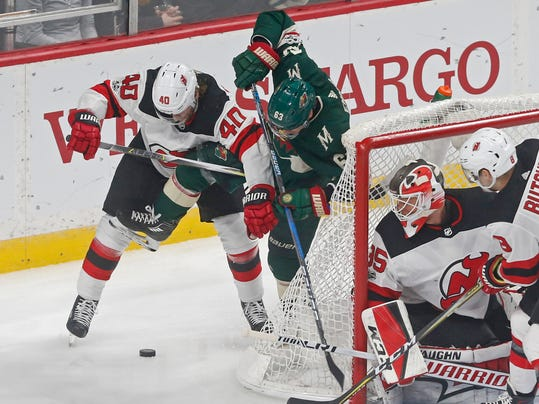 New Jersey Devils' Blake Coleman, left, and Minnesota Wild's Tyler Ennis jostle for the puck as goalie Cory Schneider, right, looks on in the first period of an NHL hockey game Monday, Nov. 20, 2017, in St. Paul, Minn. (AP Photo/Jim Mone)