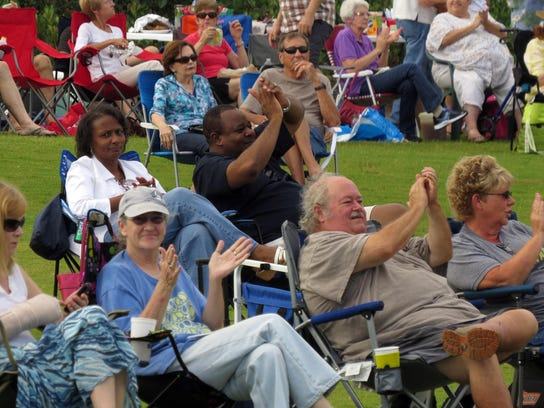 Audience members applaud during a performance as part