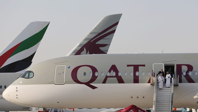 The tail of an Emirates airline plane can be seen to the left of two aircraft of Qatar Airways.