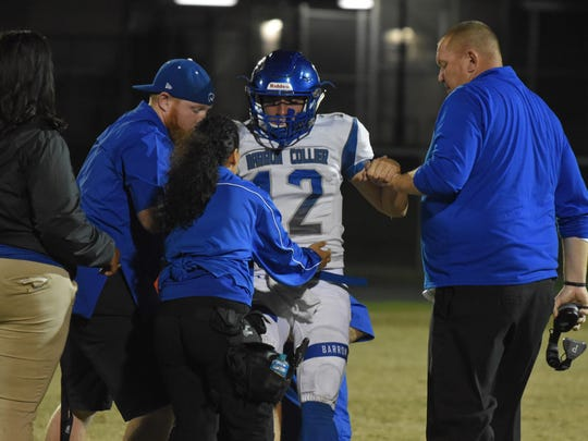 Barron Collier QB Jacob Kuhlman (12) is helped off the field after an injury in the 4th quarter during the game against Largo in the 2017 Florida High School Football Playoff Brackets: FHSAA - Class 6A tournament in Largo, Florida on Friday, Nov. 10, 2017.