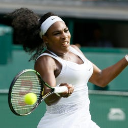 Serena Williams returns to Heather Watson of Britain, during their singles match at Wimbledon.