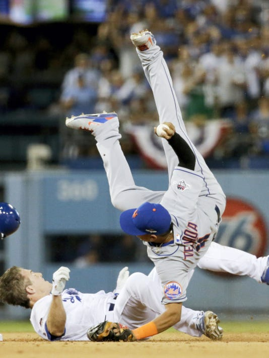 New York Mets' shortstop Ruben Tejada goes over the top of Los Angeles Dodgers' Chase Utley, who broke up a double play during the seventh inning in Game 2 of the National League Division Series on Saturday in Los Angeles.