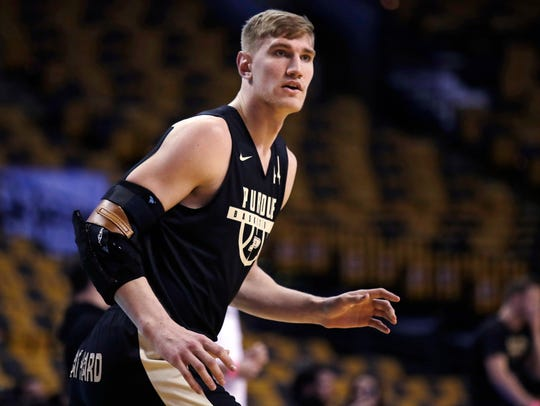 Purdue's Isaac Haas, wearing an arm brace, awaits a
