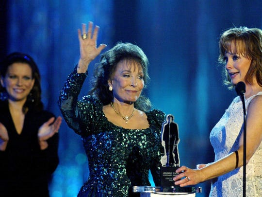 Loretta Lynn, center, waves to the crowd after been named winner of the Johnny Cash Visionary Award as presenters Martina McBride, left, and Reba McEntire look on during the CMT Country Music Awards on April 11, 2005.