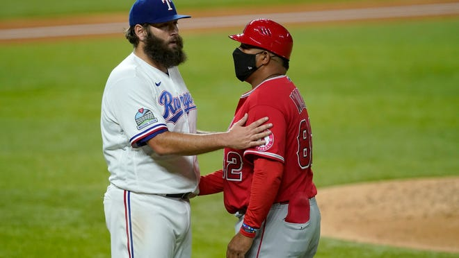 Texas Rangers' Lance Lynn talks with Los Angeles Angels first base coach Jose Molina after getting the third out in the fourth inning of a baseball game in Arlington, Texas, Tuesday, Sept. 8, 2020. Lynn hit Justin Upton with a pitch and Upton left the game. (AP Photo/Tony Gutierrez)