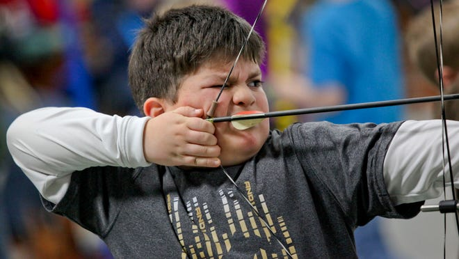 Andres Campos, 8, of Port Huron aims his bow at a target during an archery class in 2014