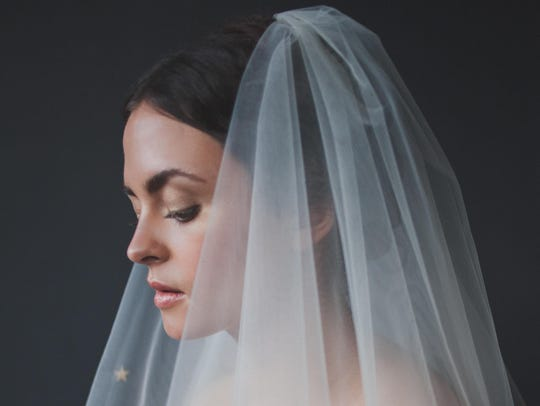 A fingertip-length tulle veil with starry trim makes