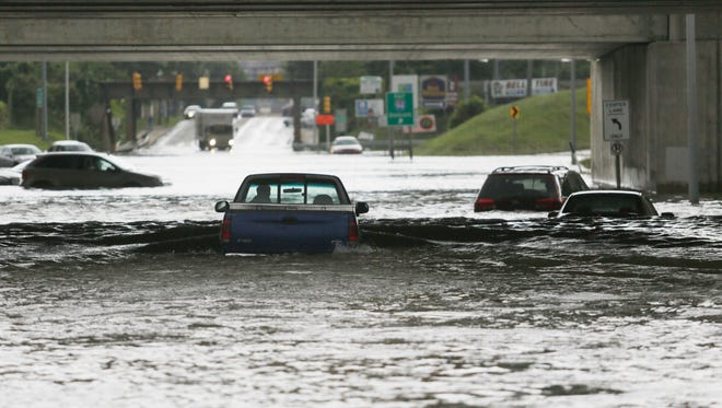 A driver chances floodwaters in Melvindale, Mich., on Aug. 12, 2014. Floods in the Detroit area were one of the USA's worst natural disasters in 2014.