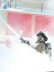 Fort Dodge firefighter Cory McFarland sprays a house