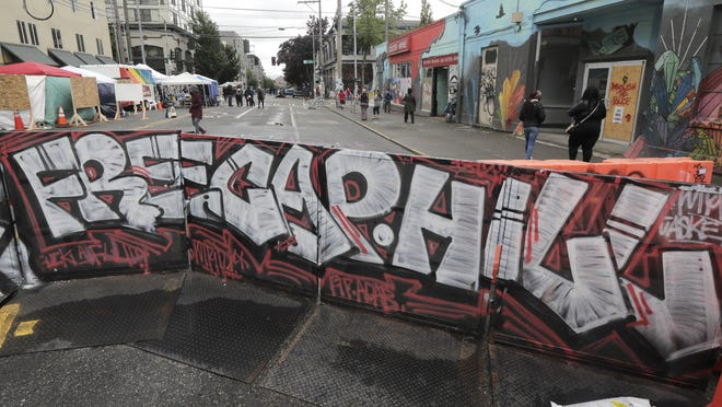 """A sign at an entrance to what has been named the Capitol Hill Occupied Protest zone in Seattle reads """"Free Cap Hill,"""" Monday, June 15, 2020. Protesters have taken over several blocks near downtown Seattle after officers withdrew from a police station in the area following violent confrontations."""
