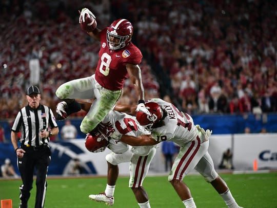 Alabama Crimson Tide running back Josh Jacobs (8) attempts to jump over Oklahoma Sooners cornerback Tre Brown (6) and linebacker Caleb Kelly (19) of the 2018 Orange Bowl college football playoff semifinal game at Hard Rock Stadium.