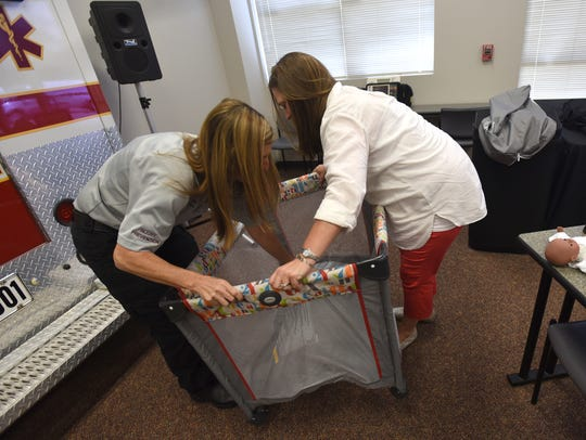 Holly Liles (right) and Kim Coburn set up a crib to