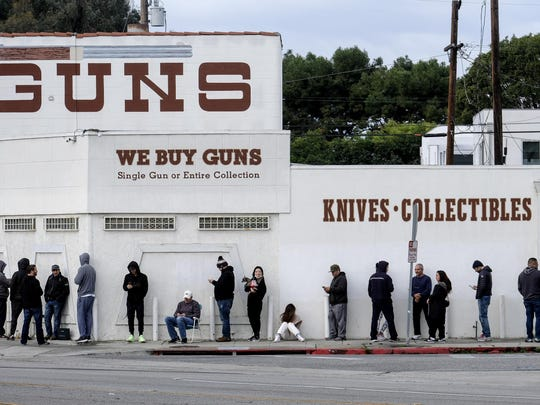 FILE - In this March 15, 2020, file photo, people wait in line to enter a gun store in Culver City, Calif. Los Angeles County Sheriff Alex Villanueva, who was sued by gun-rights groups after trying to shut down firearms dealers in the wake of coronavirus concerns, said Monday, March 30, that he is abandoning the effort. (AP Photo/Ringo H.W. Chiu, File)