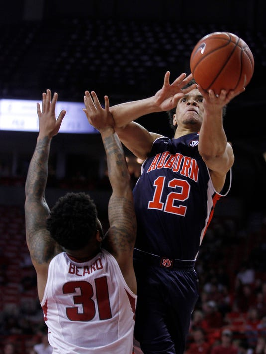 Arkansas' Anton Beard (31) cannot stop Auburn's Tyler Harris (12) from making a layup during the second half of an NCAA college basketball game Wednesday, Feb. 17, 2016, in Fayetteville, Ark. Auburn beat Arkansas 90-86. (AP Photo/Samantha Baker)