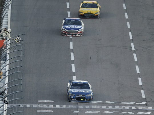 Jimmie Johnson (48) takes the checked flag winning the NASCAR Sprit Cup Series auto race in front David Gilliland (38) and Trevor Bayne (6) at Texas Motor Speedway in Fort Worth, Texas, Sunday, Nov. 8, 2015. (AP Photo/Tim Sharp)