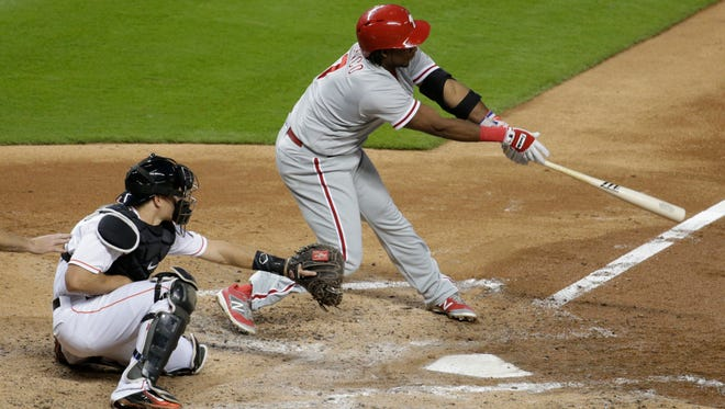 Philadelphia Phillies' Maikel Franco, right, hits a double as Miami Marlins catcher J.T. Realmuto looks on during the third inning Friday.
