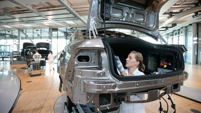 An employee of German car maker Volkswagen working on a car at the company's Dresden, Germany, plant.