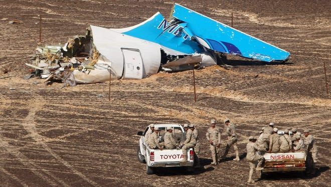 Egyptian servicemen approach a piece of wreckage of Russian MetroJet Airbus A321 at the site of the crash in Sinai, Egypt, 01 November 2015.