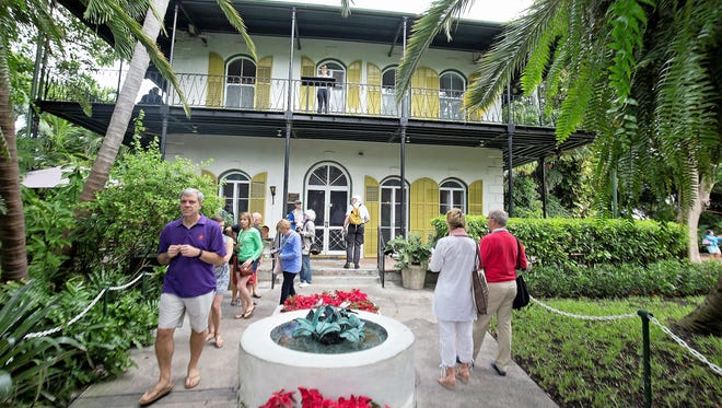 Visitors stroll on the entrance path of the Ernest Hemingway Home & Museum in Key West, Fla., Monday, Jan. 6, 2016. A facet of the prize for the winner of the Florida Keys Flash Fiction literary contest is the opportunity to spend up to 10 days writing in the same study that Hemingway utilized when he lived and wrote at the house in the 1930s.