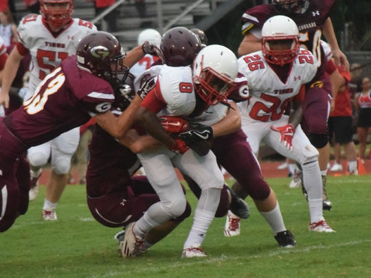 Tioga senior Markenzie Taylor (8) breaks a few tackles against Grant at the Pineville Jamboree Friday.