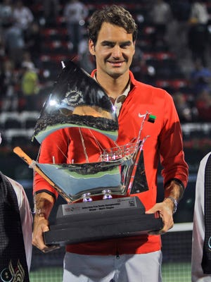 Roger Federer displays his trophy after beating Tomas Berdych of Czech Republic during the final match of the Dubai Duty Free Tennis Championships.