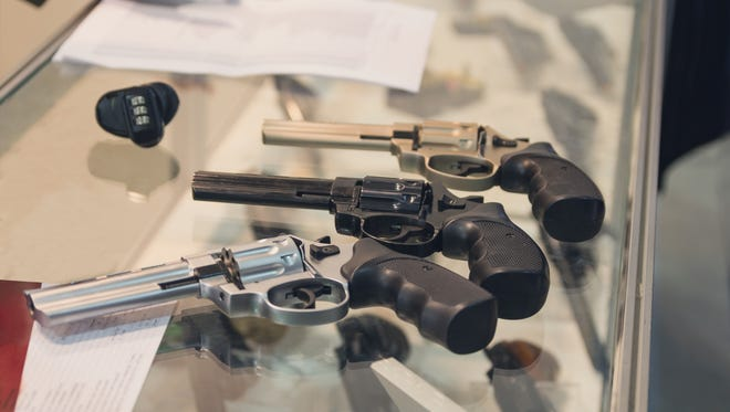 Revolvers sit on the counter of a gun shop.