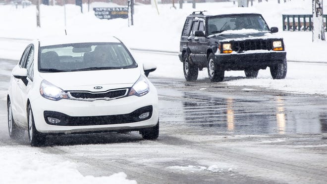 Drivers battled snowy conditions Monday, as seen here, and icy spots Tuesday morning after freezing rain fell in the early morning hours.