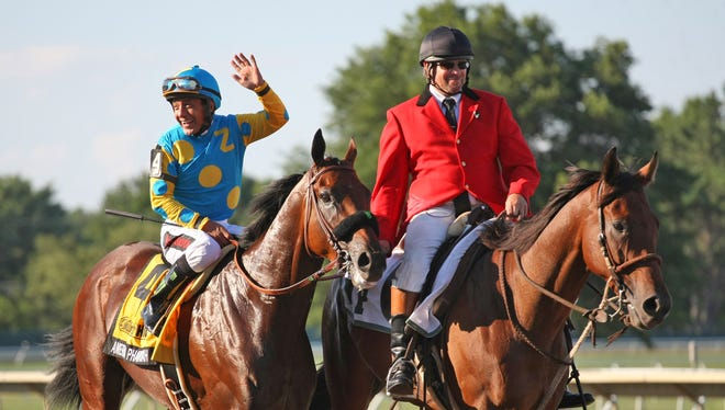 Jockey Victor Espinoza waves to the crowd aboard American Pharoah after winning the $1,750,000 Grade 1 William Hill Haskell Invitational at Monmouth Park in Oceanport, New Jersey on Sunday, Aug. 2, 2015.  (Ryan Denver/EQUI-PHOTO via AP)