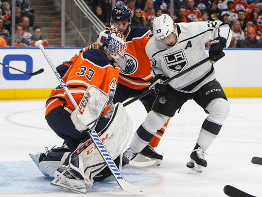Los Angeles Kings' Dustin Brown (23) and Edmonton Oilers' Darnell Nurse (25) battle in front of the net as goalie Cam Talbot (33) makes the save during the first period of an NHL hockey game, Tuesday, Jan. 2, 2018, in Edmonton, Alberta. (Jason Franson/The Canadian Press via AP)