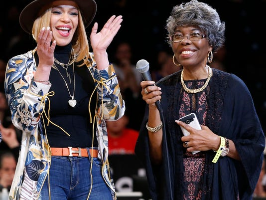 Singer Faith Evans, left, applauds Violetta Wallace, mother of Brooklyn-born Biggie Smalls, also known as The Notorious B.I.G., during a tribute to Smalls before the first half of an NBA basketball game between the Brooklyn Nets and the New York Knicks, Sunday, March 12, 2017, in New York. Smalls died 20 years ago on March 9, 1997. (AP Photo/Kathy Willens)