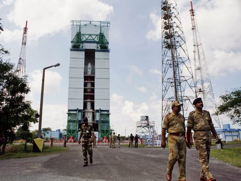 Central Industrial Security Force (CISF) personnel walk near the Polar Satellite Launch Vehicle (PSLV ��� C25) at the Satish Dhawan Space Center at Sriharikota, in the southern Indian state of Andhra Pradesh.
