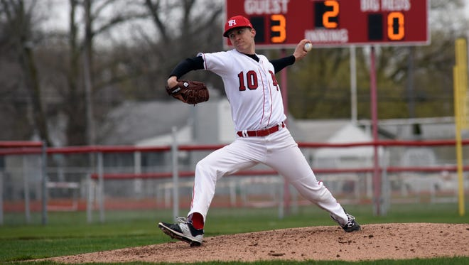 Big Reds' Brett Wagner tosses in a pitch Monday, April 17, during boys baseball action against St. Clair at Port Huron High School.