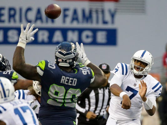 Indianapolis Colts quarterback Jacoby Brissett (7) passes under pressure from Seattle Seahawks defensive tackle Jarran Reed (90), in the first half of an NFL football game, Sunday, Oct. 1, 2017, in Seattle. (AP Photo/Elaine Thompson)